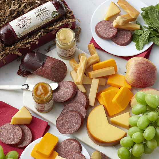 Gift box includes beef summer sausage, smoked cheddar cheese, farmhouse cheddar cheese, smoked gouda, honey & pineapple mustard, and sweet hot mustard
