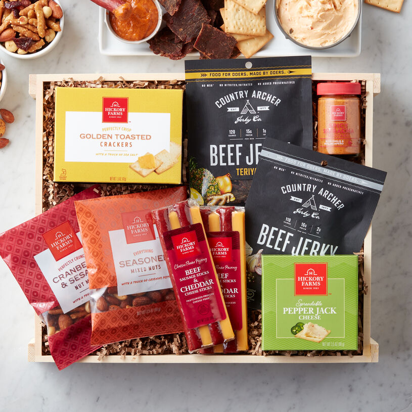 This crate is packed with original and teriyaki Country Archer beef jerky, meat & cheese sticks, Spreadable Pepper Jack Cheese, Sriracha mustard, mixed nuts, and naan crisps.