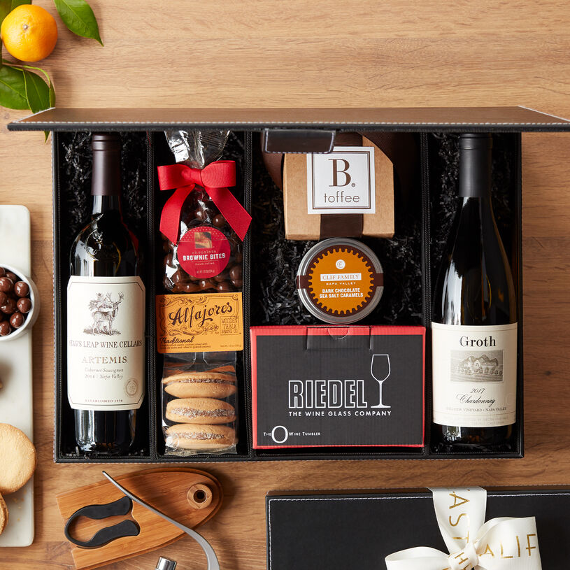 Share a journey through Napa Valley with this impressive wine gift filled with decadent treats, two Riedel stemless wine glasses, lever-style corkscrew wine opener, and a handsome black wine box.