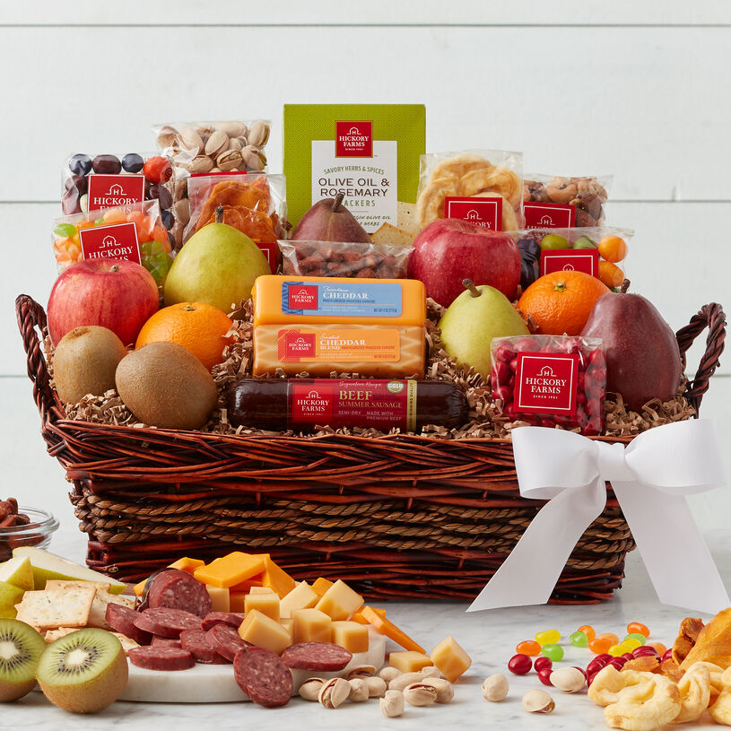 This gift basket is filled with fruit, summer sausage, cheese, crackers, mixed nuts, dried fruit, and a cookie.