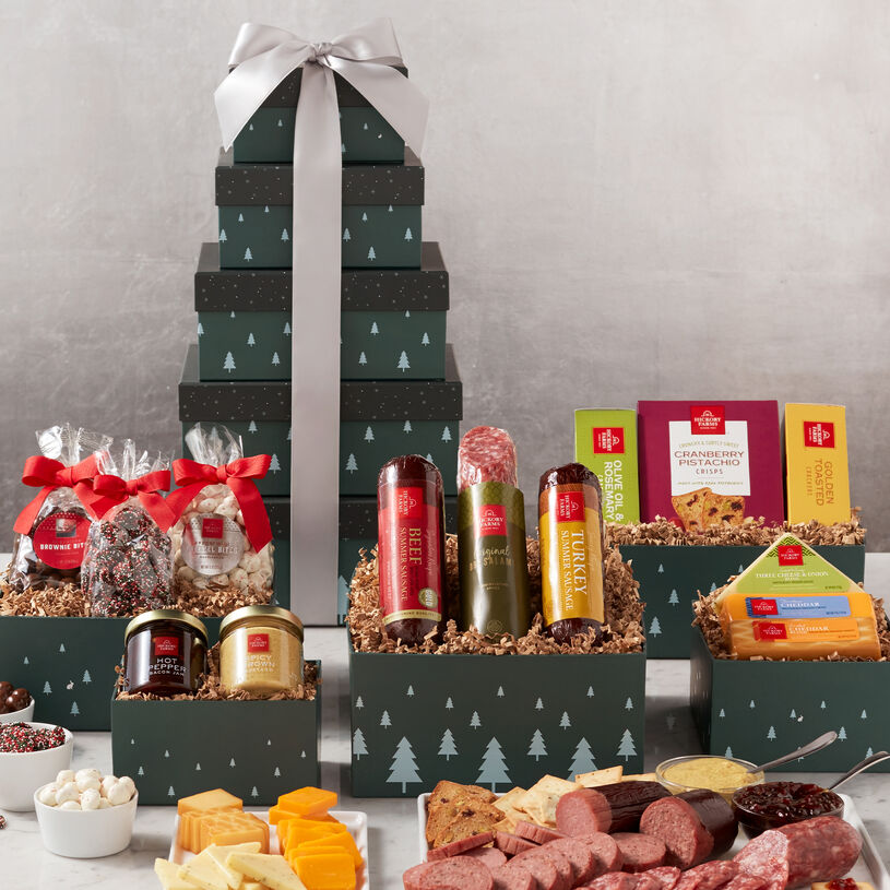 This holiday gift tower includes five impressively beautiful green boxes patterned with white holiday trees filled with sausage, cheese, crackers, and chocolate treats.