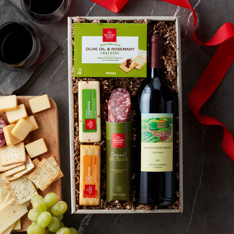 The Hickory Farms Wine & Savory Snack Collection includes a bottle of wine, salami, cheese, and crackers.