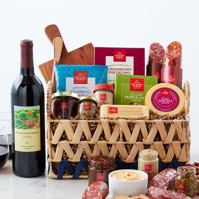 This basket is filled with savory salami, cheeses, mustard, chutney, tapenade, crackers, cheese board and spreader, and a bottle of wine