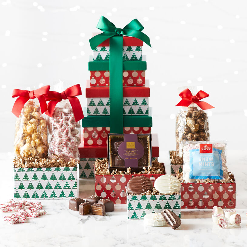This gift tower includes five festive holiday boxes filled with Dark Chocolate Sea Salt Caramels, Snowflake Pretzels, Snow Mints, Popcorn, White Chocolate Covered Sandwich Cookie, and Milk Chocolate Covered Sandwich Cookie.