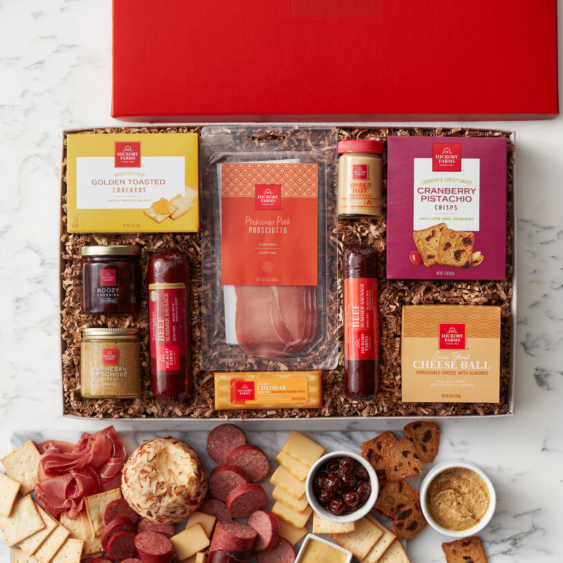 It includes Signature Beef and Spicy Beef Summer Sausages, Premium Pork Prosciutto, Swiss Blend Cheese Ball, Smoked Cheddar Blend, Cranberry Pistachio Crisps, Artichoke Parmesan Dip, Boozy Cherries, Sweet Hot Mustard, and Golden Toasted Crackers.