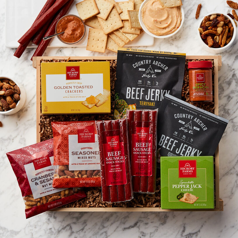 This crate is packed with Country Archer Original and Teriyaki Beef Jerky, Beef Sausage Snacks, Spreadable Pepper Jack Cheese, Spicy Sriracha Mustard, mixed nuts, and Golden Toasted Crackers.