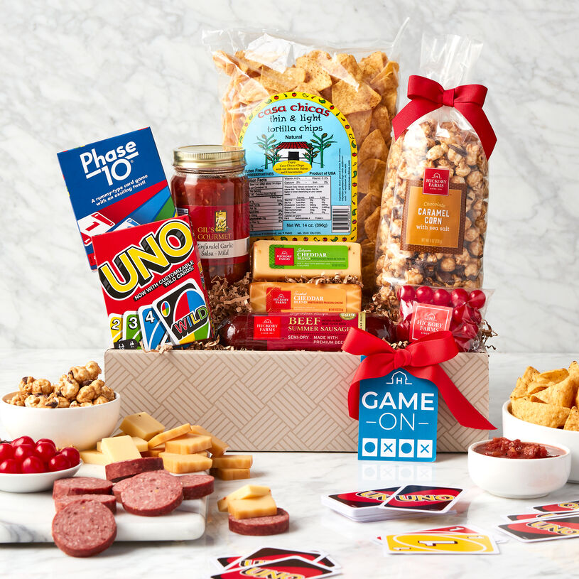 Gift set filled with snacks like summer sausage, cheese, tortilla chips, salsa, chocolate caramel corn, and Cherry Sours. Plus, UNO and Phase 10 games.