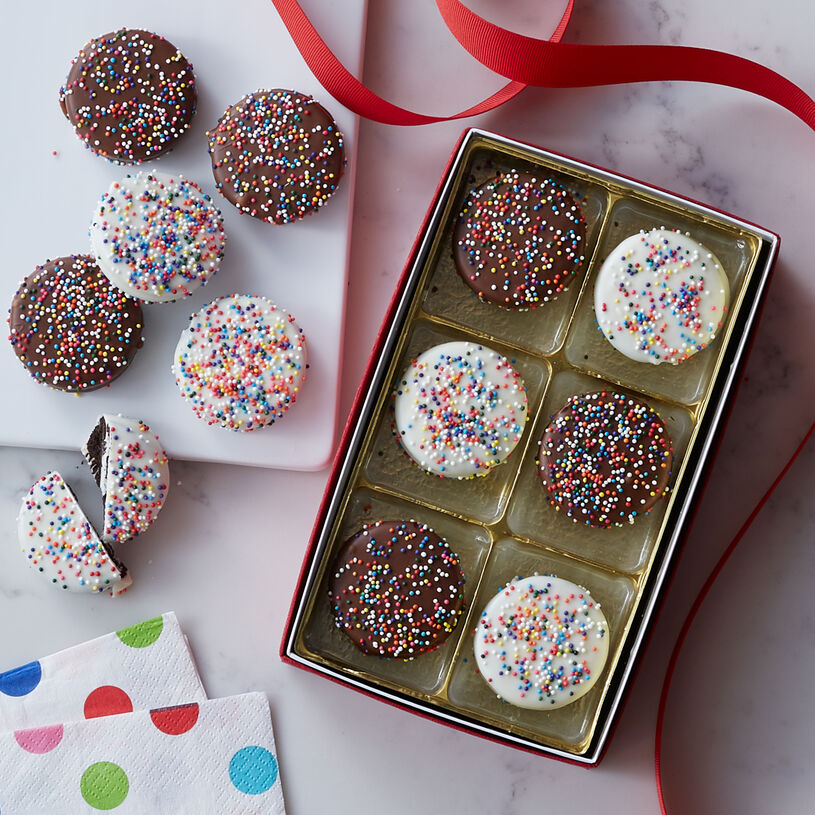 Crispy chocolate cookies filled with luscious cream, then dipped in white or milk chocolate. Colorful sprinkles add a festive touch that make these perfect for celebrating.