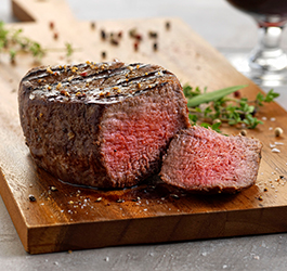 Medium rare steak filet cut open and displayed on a cutting board.