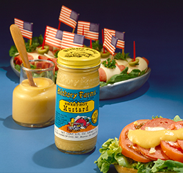 Jar of sweet hot mustard next to plate of rolled up summer sausage with American Flag toothpick decorations in 1970's.