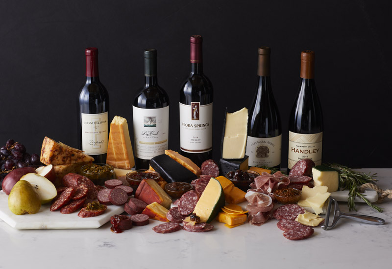 A charcuterie spread of cured meats, cheeses, and fruits in front of a variety of red wine bottles