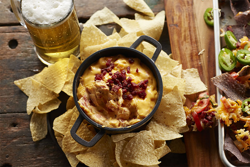 A bowl of yellow queso with chopped up beef summer sausage on top and a glass of beer
