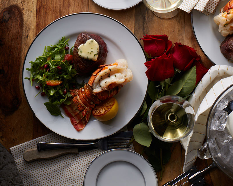 Two surf and turf dinners with compound butter and a glass of white wine