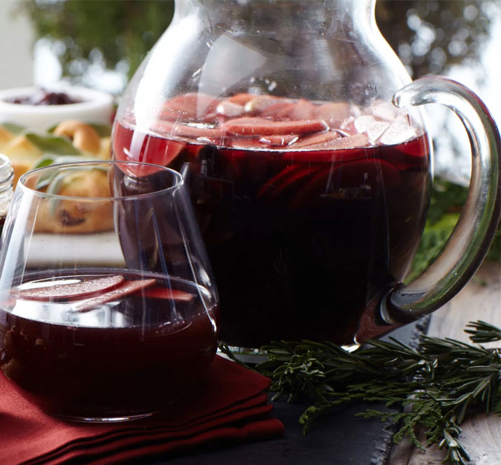 Pitcher of cherry apple sangria with a jar of Hickory Farms Hot Pepper Bacon Jam for Holiday Recipe Guide