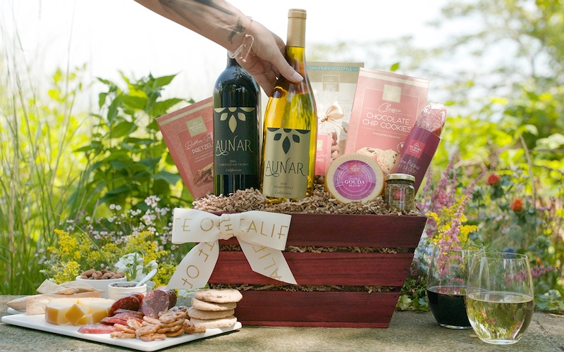 Image of wine in a wicker basket with wrapped gifts in front of a photo backdrop
