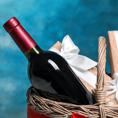 red wine bottle in basket with blue background