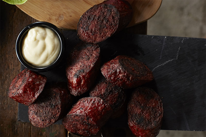 Sliced up grilled beef summer sausage with a side dish of horseradish dipping sauce for game day