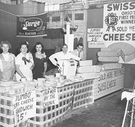 Richard Ransom and family posing behind cheese counter at local fair in the early 1950's.