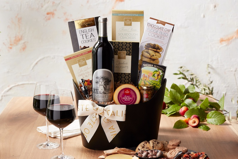 woman setting down a gift box of wines, meats, cheeses, and crackers from Hickory Farms