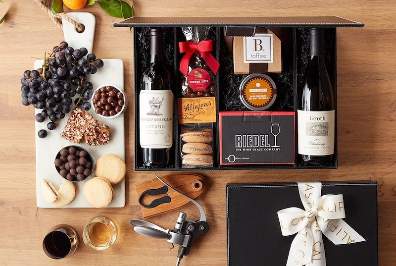 Picture of marble cheese board with popular fruit and sweet pairings, a wine gift box, and wine accessories like a bottle opener