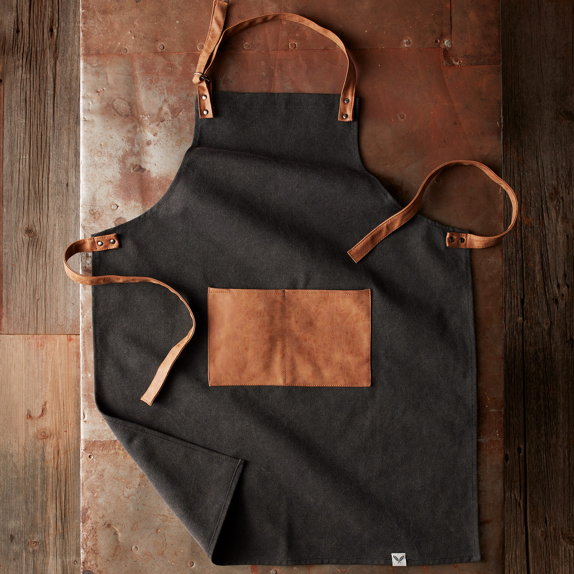 Made of durable black canvas with faux leather straps and pocket, this apron will keep your favorite grillmaster clean and stylish at every barbeque